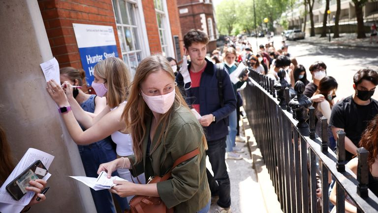 People fill in paperwork while queueing outside a vaccination centre for young people and students at the Hunter Street Health Centre, amid the coronavirus disease (COVID-19) outbreak, in London, Britain, June 5, 2021. REUTERS/Henry Nicholls