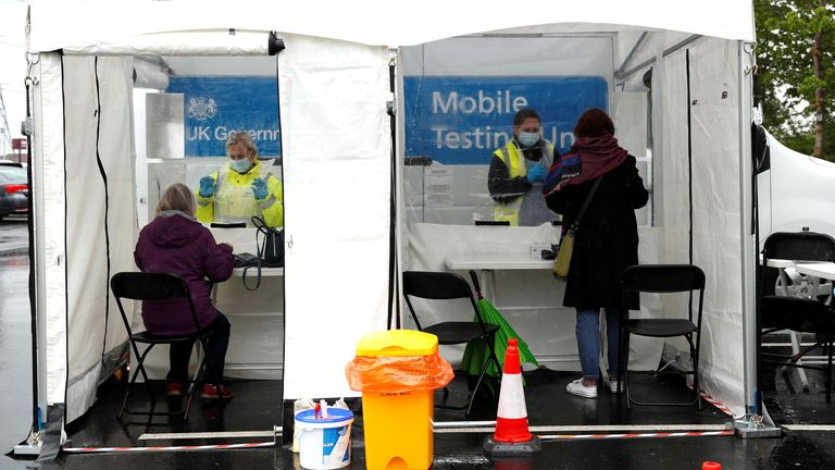 People visit an NHS mobile vaccination and testing unit at Northumberland Retail Park