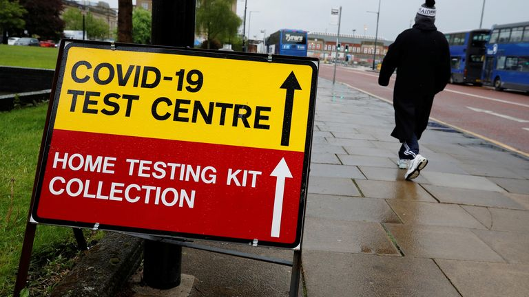 A man walks past a sign directing people to a testing station, amid the outbreak of the coronavirus disease (COVID-19) in Bolton, Britain, May 17, 2021