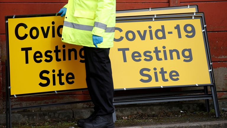 A member of NHS Test and Trace staff sets up a mobile testing centre in the Moston area of Manchester