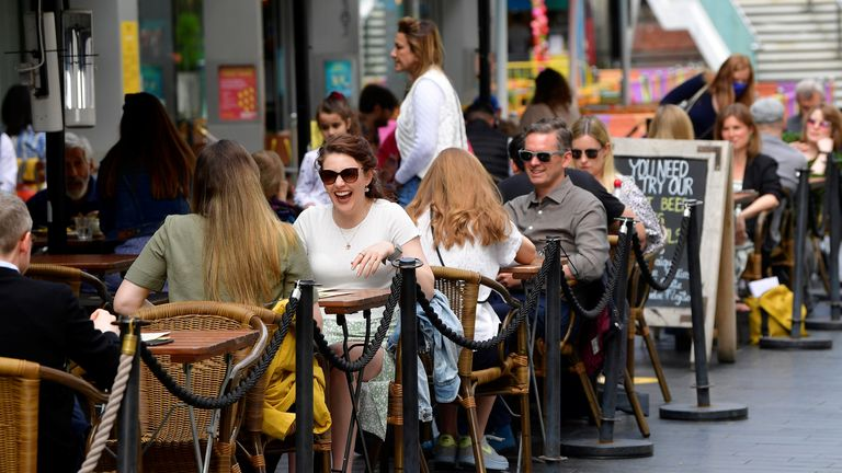 People relax at outdoor dining areas as lockdown restrictions continue to ease in London
