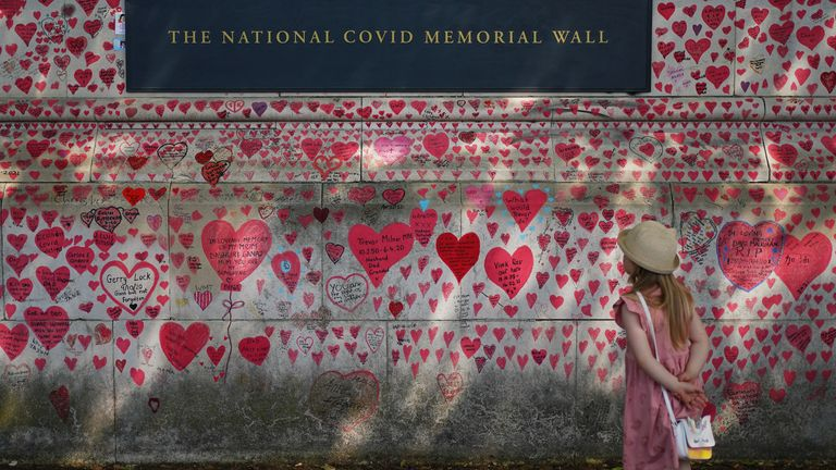 A child looking at the National Covid Memorial Wall on the Embankment in London