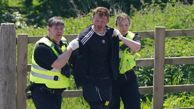 A man is detained at Hallington House Farm, on the outskirts of Louth, Lincolnshire, by officers hunting for Daniel Boulton, who is sought in connection with the deaths of a 26-year-old woman and her nine-year-old son on Monday. (Joe Giddens/PA)