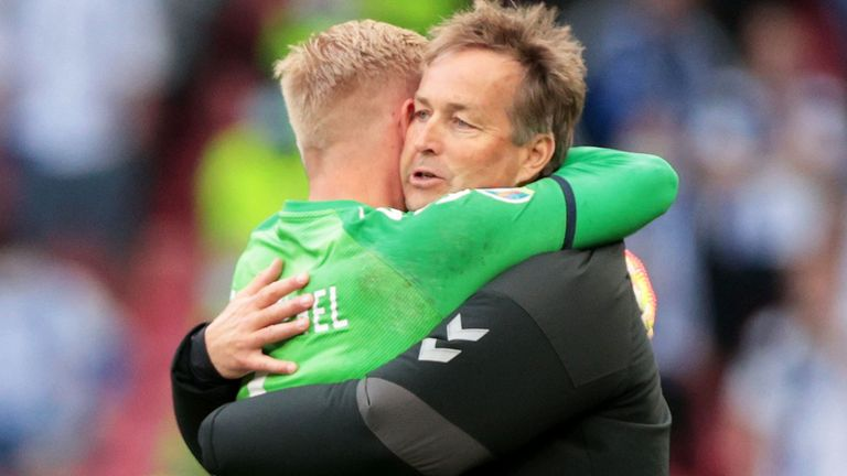 Denmark coach Kasper Hjulmand embraces his goalkeeper Kasper Schmeichel, who has also been praised for his response to what happened to Eriksen