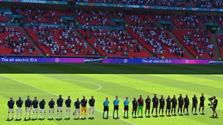 Both teams line up to sing their national anthems. Pic: AP