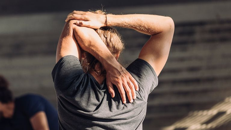 Man stretches his arm while warming up for an outdoor cardio workout.