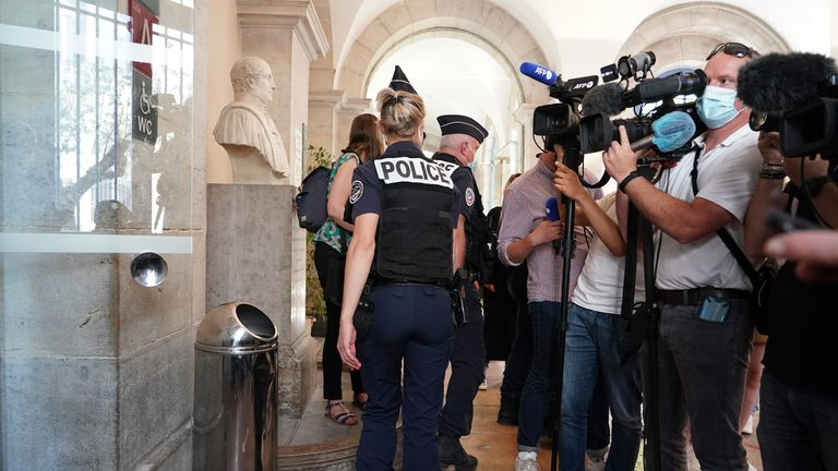 """Police officers leave the courtroom as the man who slapped French President Emmanuel Macron is tried, Thursday, June 10, 2021 in Valence, central France. The 28-year-old Frenchman who described himself as a right-wing or extreme-right """"patriot"""" was sentenced to four months in prison Thursday for slapping President Emmanuel Macron in the face. (AP Photo/Laurent Cirpriani)"""