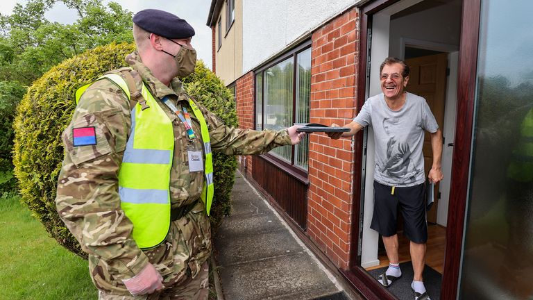 A member of the armed forces hands a testing kit to a resident in Bolton
