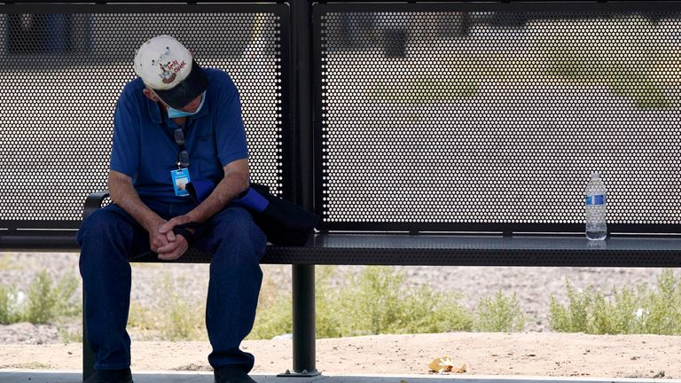 A person waits for a bus in the shade amid sweltering heat in Phoenix. Pic: AP