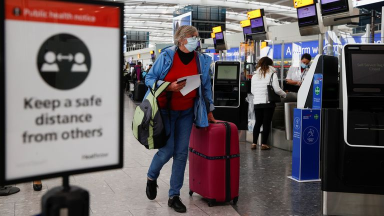 A passenger walks with her luggage at the Terminal 5 departures area at Heathrow Airport in London
