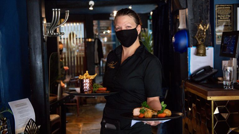 A waitress carries meals to a table during service at Loxleys Restaurant & Wine Bar in Stratford, Warwickshire, as indoor hospitality and entertainment venues reopen to the public following the further easing of lockdown restrictions in England. Picture date: Monday May 17, 2021.