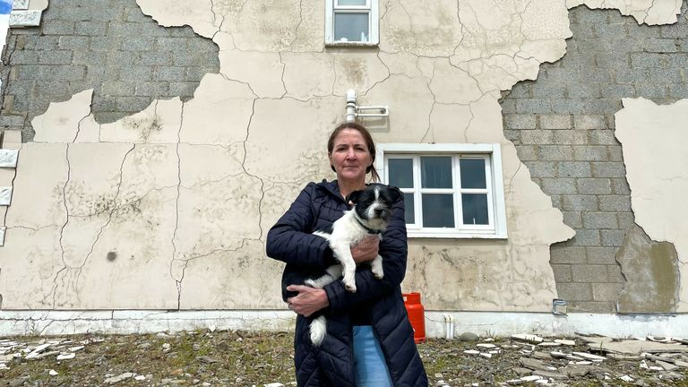 Joanne McLaughlin and her dog Bonnie in front of her crumbling house in Ireland