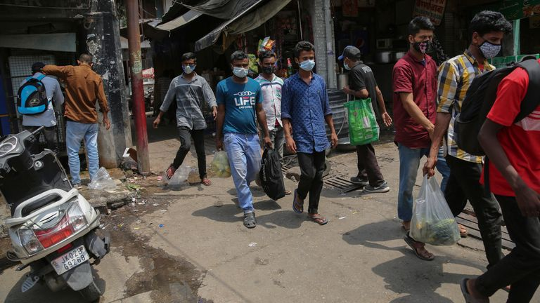 Indian people wearing masks and walk for  transport during the relaxation days of a lockdown to curb the spread of COVID-19, at Bus stand in Jammu, India, Monday, June.7, 2021.(AP Photo/Channi Anand)