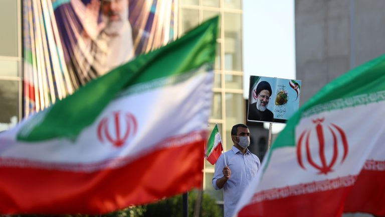 A supporter of Ebrahim Raisi holds a poster of him during an rally in Tehran