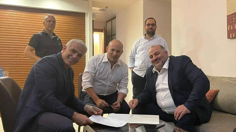 The deal being signed, with Yair Lapid,  a secular centrist on the left. In the middle is Naftali Bennett, a hard line nationalist, and on the right, Mansour Abbas, an Islamist Arab. Pic: Nawaf Alnabary, Kan news