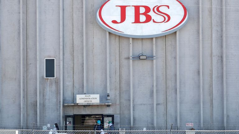 Employees walk around with face masks at the JBS USA meat packing plant, which on Monday was closed after numerous employees tested positive and two have died from the coronavirus disease (COVID-19), in Greeley, Colorado, U.S., April 14, 2020