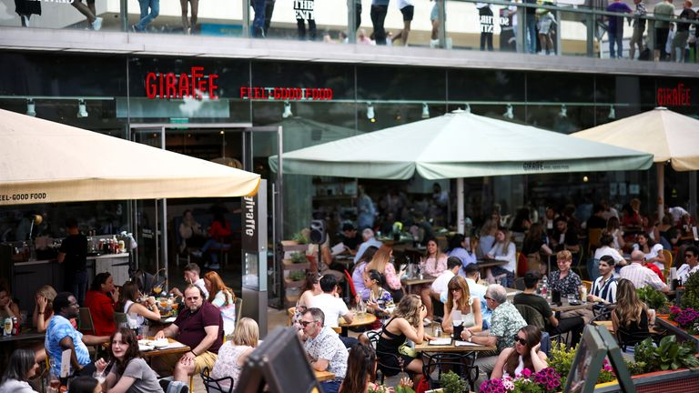 People sit at an outdoor restaurant on the South Bank during sunny weather, amid the coronavirus disease (COVID-19) outbreak, in London, Britain, June 5, 2021. REUTERS/Henry Nicholls/File Photo