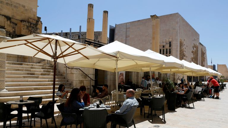 People sit at an outdoor restaurant as restaurants and markets reopened for business after coronavirus disease (COVID-19) vaccinations reached 60% of the adult population, in Valletta, Malta May 10, 2021. REUTERS/Darrin Zammit Lupi/File Photo