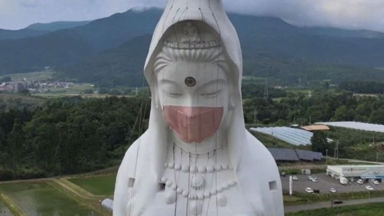 Enormous mask is placed on 187-feet-high statue in Japan