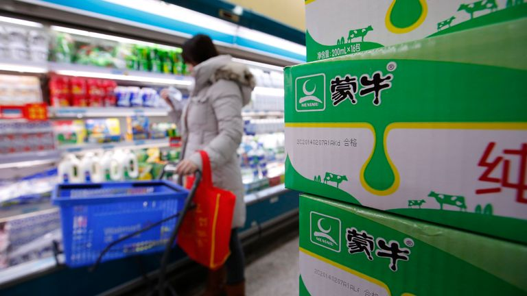 Cartons of Mengniu's milk products (R) are placed at a supermarket in Beijing February 13, 2014.