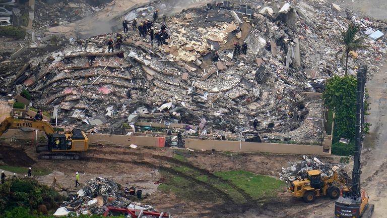 Gambar udara ini menunjukkan petugas pencarian dan penyelamatan yang bekerja di lokasi sebuah gedung apartemen tepi laut yang sebagian runtuh, setidaknya satu orang tewas dan lebih dari 100 orang hilang, di Surfside, Florida, Jumat, 25 Juni 2021 (AP Photo/Gerald) Herbert)