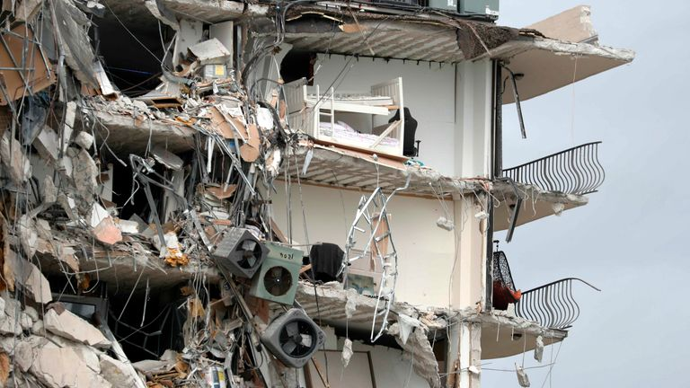 Items and debris dangle from a section of the oceanfront residential building. Pic AP