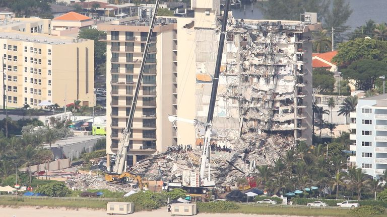Aerial view shows the partially collapsed residential building as cranes work at the site in Surfside near Miami Beach, Florida, U.S. June 27, 2021