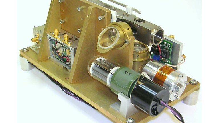 A laboratory representation of the Deep Space Atomic Clock, with a quarter alongside the unit for size comparison, and without the electronics required for operation. It also contains laboratory components, including a metal frame, instead of flight hardware. At just under 0.2 cubic feet and weighing about 7 pounds, the clock is smaller, lighter an