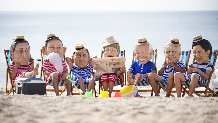 Oxfam campaigners pose as G7 leaders on Swanpool Beach near Falmouth, Cornwall. The charity is calling on the G7 countries to commit to cutting emissions further and faster and provide more finance to help the most vulnerable countries respond to the impacts of climate change. Picture date: Saturday June 12, 2021.