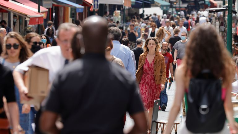 People walk without face masks in Paris after the relaxing of rules -but there are now fears the country is set for a fourth wave of COVID cases