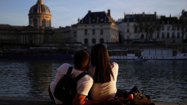 A couple enjoy the sunset on the Seine river bank, in Paris, Monday, March 29, 2021. (AP Photo/Thibault Camus)
