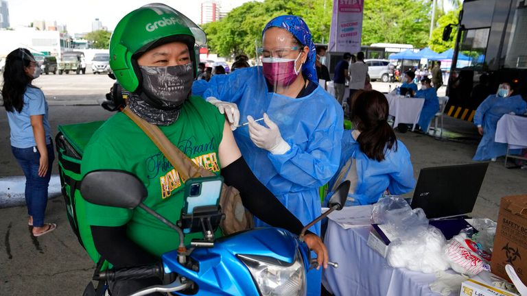 A food delivery driver gets a drive-thru vaccine in Manilla on Tuesday. Pic: AP