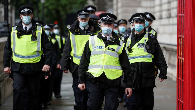 Police attend an anti-lockdown protest in London
