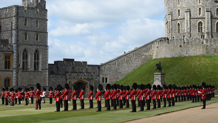 Guardsman stand in formation in front of the Queen in the quadrangle at Windsor