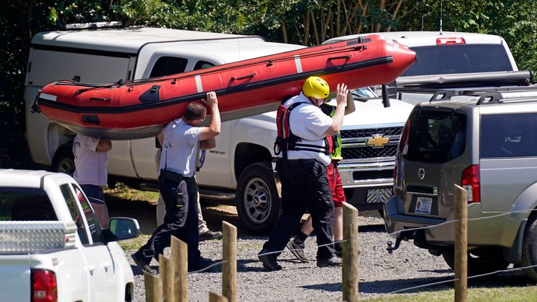 Rescue workers carry a boat near the Dan River during the search for the two missing people