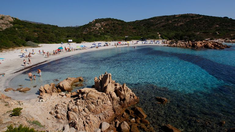 """People stand at the Ramizzo beach in the so called """"Emerald Coast"""" of the Sardinia island in Italy July 7, 2011"""
