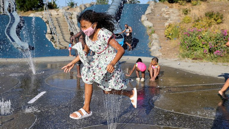 A girl jumps across a sprinkler at Jefferson Park in Seattle