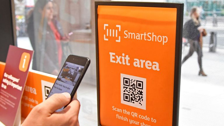 A customer uses his smartphone to pay for shopping at the first 'till-free' Sainsbury's store in London, Britain