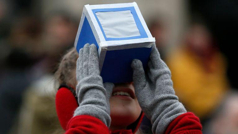 دختری هنگام کسوف جزئی خورشید در گرینویچ ، جنوب شرقی لندن ، 20 مارس 2015 یک جعبه محافظ خانگی در مقابل رصدخانه سلطنتی در دست دارد. REUTERS / Stefan Vermouth