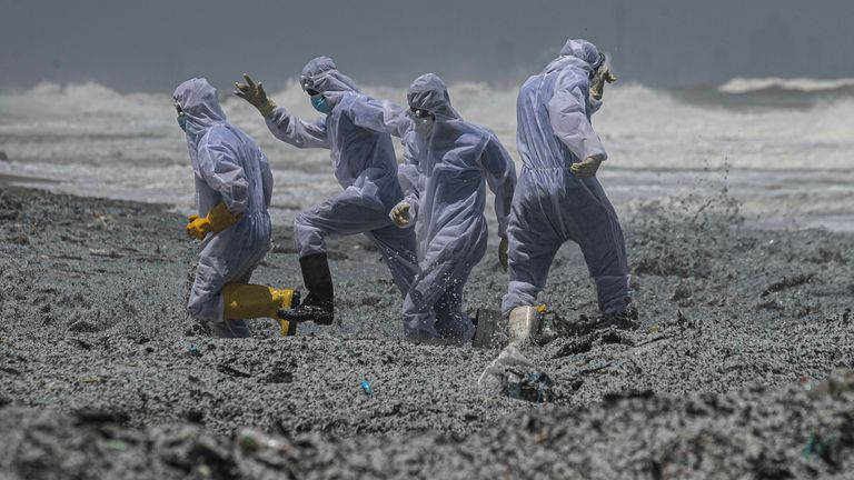 Sri Lankan navy soldiers clad in protective suits attempt to evade a wave drifting debris ashore from the burning Singaporean ship MV X-Press Pearl off Colombo port at Kapungoda, Sri Lanka, Thursday, May 27, 2021. Pic: AP