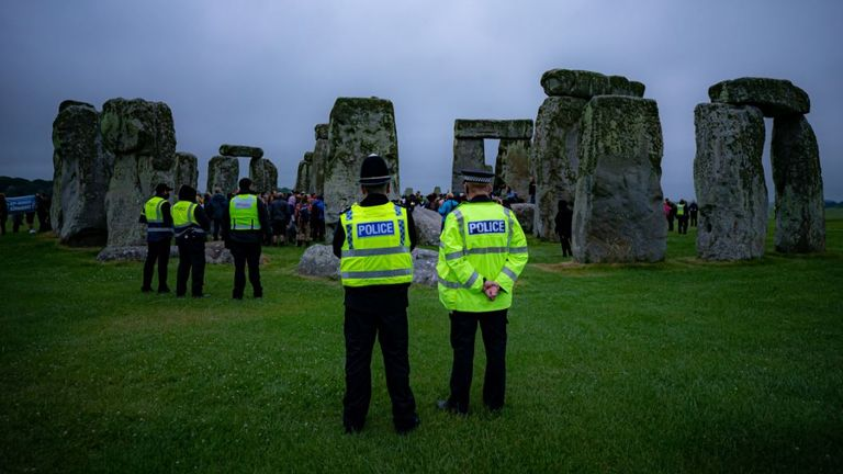 People climb over the fence and past security staff to mark the longest day of the year at Stonehenge