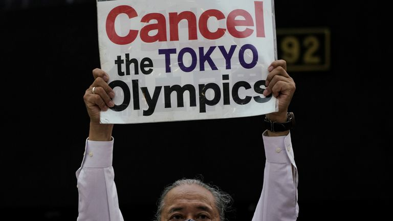 An anti-Olympics group member holds up a banner during a protest rally