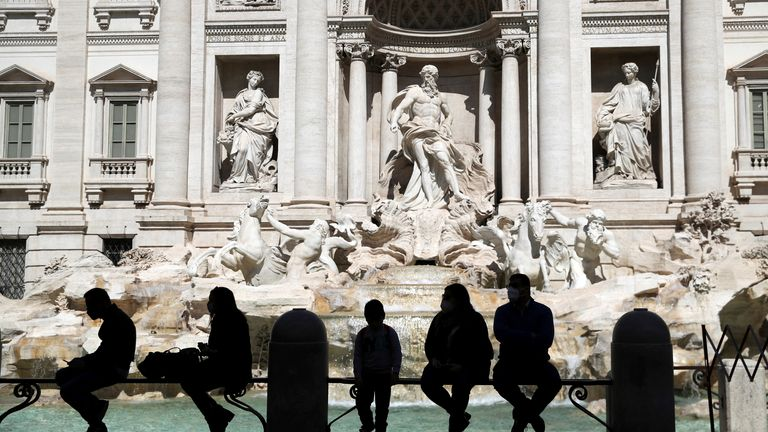 FILE PHOTO: People sit in front of Trevi's Fountain as COVID-19 restrictions in the Lazio region are slightly relaxed, in Rome, Italy March 30, 2021. REUTERS/Yara Nardi/File Photo