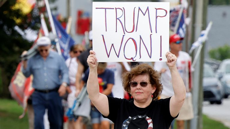 Trump supporters holding placards saying he won elections