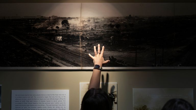 A woman points at a picture of devastation from the Tulsa Race Massacre in a prayer room at the First Baptist Tulsa church
