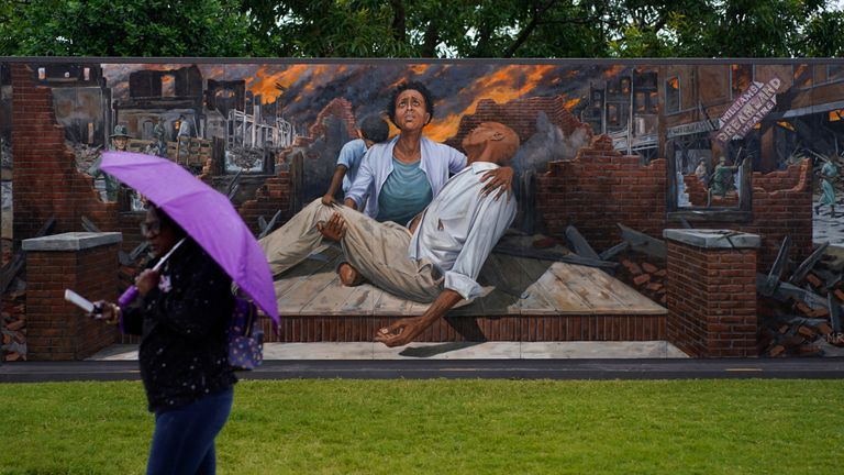 A woman walks by a mural depicting the Tulsa Race Massacre during its centennial. Pic AP