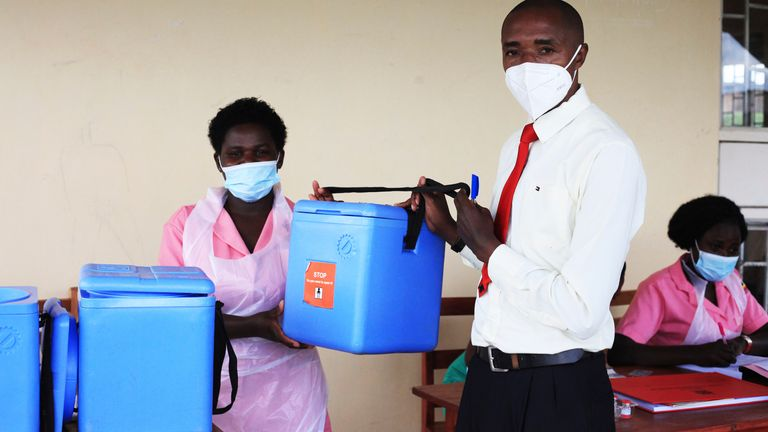 Dr Edward Arineitwe, a health worker, hands over COVID-19 vaccines to a nurse at a health centre in Uganda. Pic: AP
