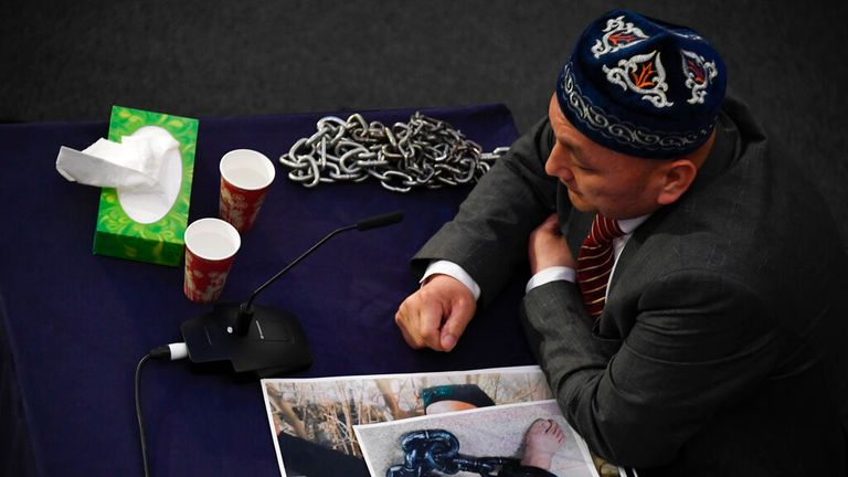 A witness gives evidence to the panel with images of people's feet in chains. Pic: AP