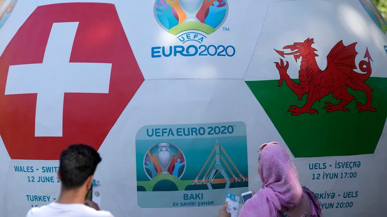 People stand by a ball advertising the upcoming Euro 2020 soccer championship displayed in Baku, Azerbaijan, Thursday, June 10, 2021. The Euro 2020 gets underway on Friday June 11 and is being played in 11 host cities across 11 countries. The event was delayed by one year after being postponed in 2020 due to the COVID-19 pandemic. (AP Photo/Darko Vojinovic)