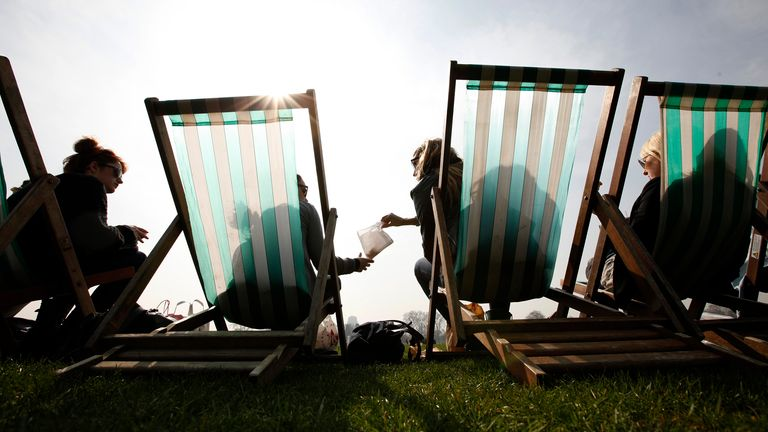 Tourists have a picnic in the park as they sit in the sun in deck chairs in Hyde Park, London